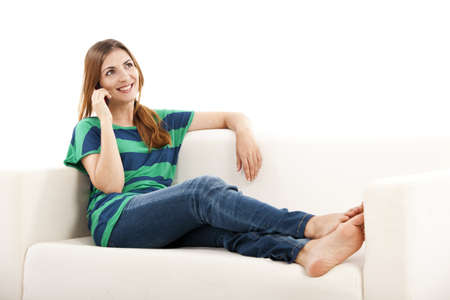 young woman sitting: Beautiful young woman sitting on a sofa and making a phone call, isolated on white Stock Photo