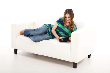 Girl lying on a sofa and using a tablet, isolated on white background Stock Photo - 12165429