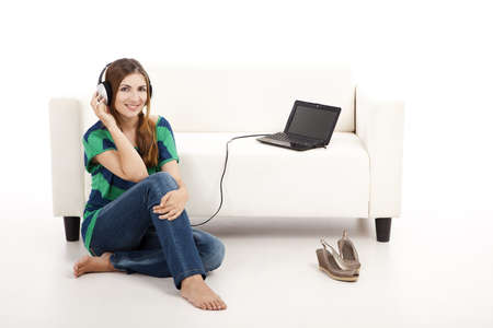 Beautiful young woman listen music on a laptop, isolated on white Stock Photo - 12165435