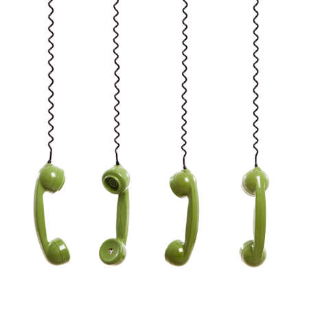 Handset piece from an old phone suspended by the phone cord, isolated on white background photo