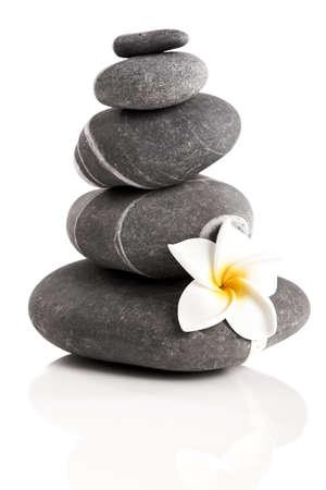 piedras zen: Piedras pirámide con una flor de Plumeria, aisladas sobre fondo blanco