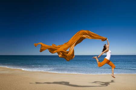 Schöne junge Frau Springen auf dem Strand mit einem farbigen Gewebe Standard-Bild