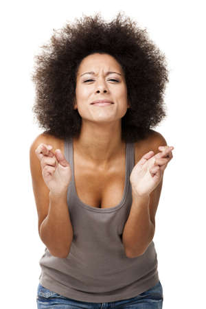 finger crossed: Afro-American young woman with fingers crossed, isolated on white Stock Photo
