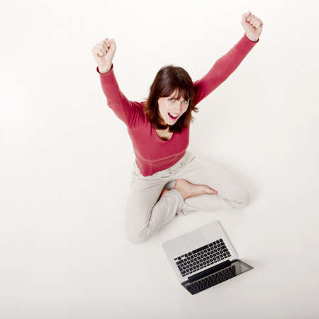 Happy woman with arms raised, sitting on the floor with a laptop Stock Photo - 12436319