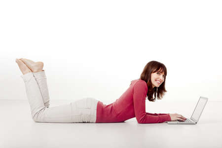 woman laptop: Beautiful woman lying on the floor and looking to the camera while working with a laptop