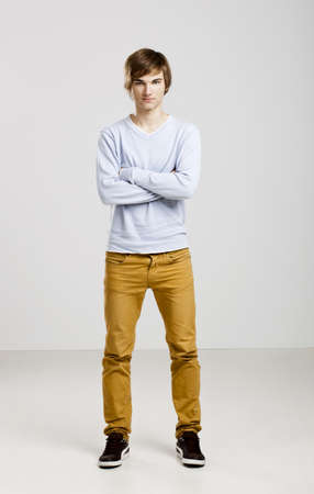 cross arms: Portrait of a handsome young man standing over a gray background