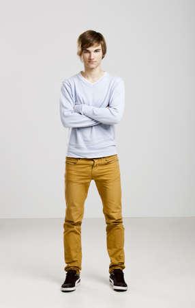 young man standing: Ritratto di un bel giovane in piedi su uno sfondo grigio Archivio Fotografico
