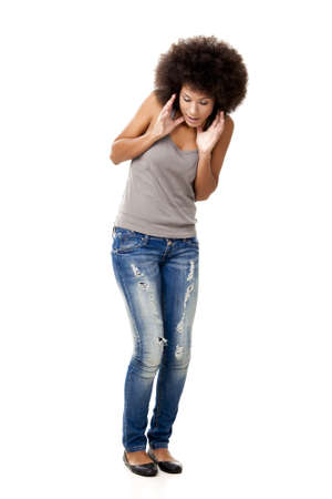 Afro-americana mujer joven mirando hacia abajo sorprende con algo, aislado en blanco