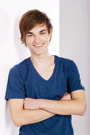 Portrait of a casual young man with a happy face, against a white wall Stock Photo - 12670054