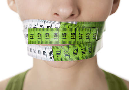 Portrait of a young  woman with a green measuring tape covering the mouth Stock Photo - 12670095