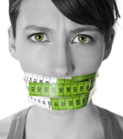fat girl: Portrait of a young  woman with a green measuring tape covering the mouth Stock Photo