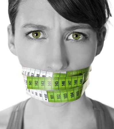sobre peso: Retrato de una mujer joven con una cinta métrica verde que cubre la boca Foto de archivo