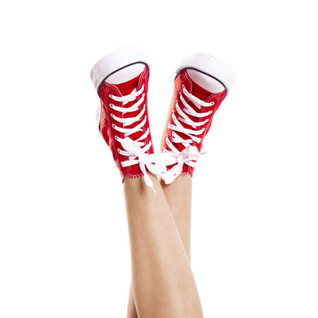 tennis shoe: Close up of woman legs wearing a pair of red sneakers, isolated on white