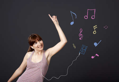 Young woman dancing and listen music with musical notes drawn with chalk on a black wall photo