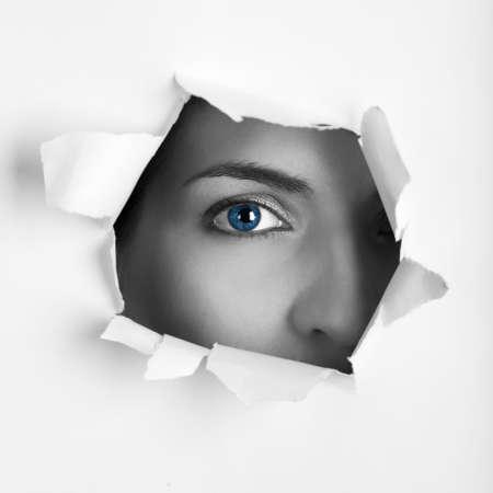 ojos azules: Hermoso ojo femenino azul mirando a través de un agujero en una hoja de papel
