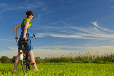 Happy girl over a bicycle and looking back, in a green meadow Stock Photo