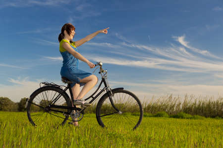 Happy girl with a old bicycle and pointing to something, in a green meadow photo