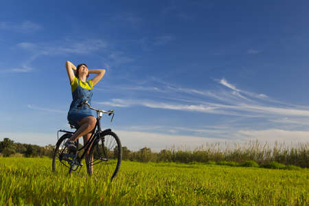 Happy girl over a bicycle and looking the view, in a green meadow Stock Photo - 12955239