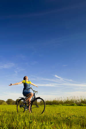 Happy girl over a bicycle and looking the view, in a green meadow photo