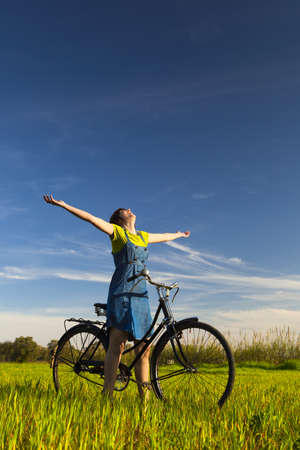 Happy girl over a bicycle and looking the view, in a green meadow Stock Photo - 12955329