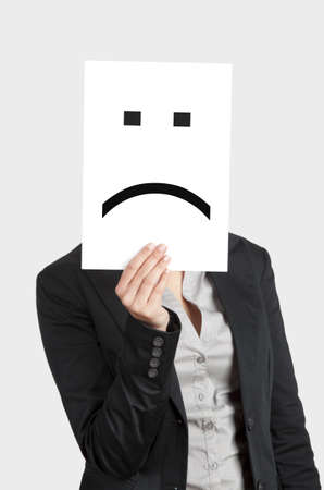 Woman showing a blank paper with a sad emoticon in front of her face Stock Photo - 12955158