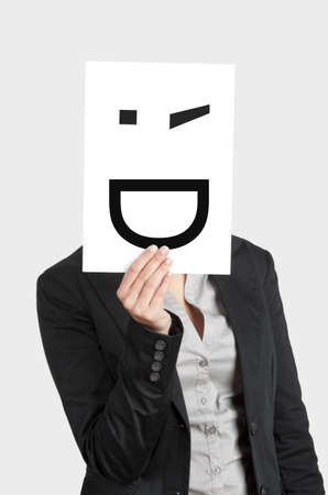 Woman showing a blank paper with a smile winking in front of her face Stock Photo