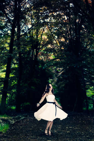 twirl: Beautiful fashion woman dancing on the forest surrounded by trees