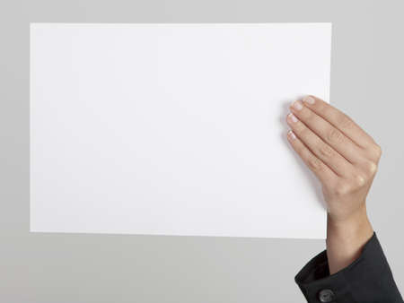 Female hand holding a blank paper sheet photo