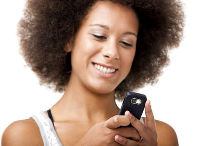 Beautiful African American woman sending a sms on cell phone, isolated on white background photo