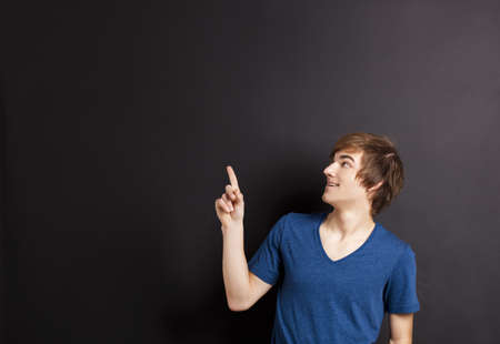 Portrait of a happy young pointing to a chalk board, with copyspace for the designer photo