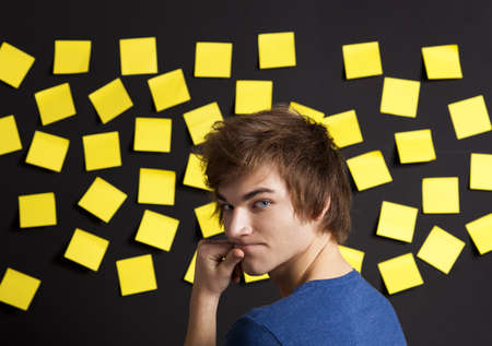 Young student in front of a board with yellow notes and looking in to the camera Stock Photo - 13359402