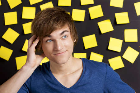 Young student thinking in front of a board full of  yellow notes photo