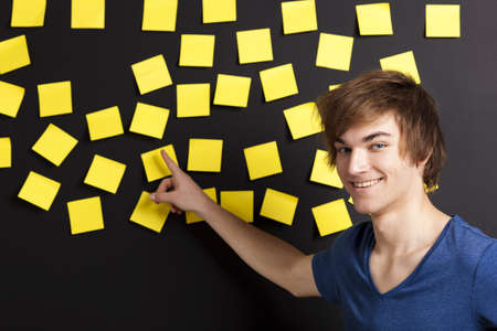 Young student pointing to a board full of yellow notes and looking in to the camera photo