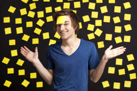 Happy student with a reminder on the head, and with more yellow paper notes in the background Stock Photo - 13359411