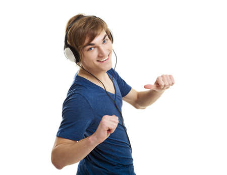 Happy young man dancing and listening music with headphones, isolated on white background  photo