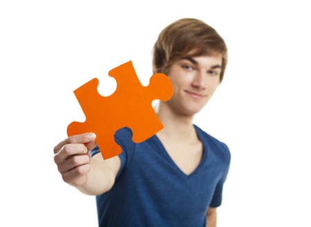 Young man holding a puzzle piece isolated on white background, soluton concept photo