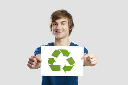 Casual young man holding a recycling sign to promote a green and better world, over a gray background Stock Photo - 13359277