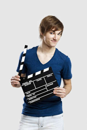 clapper board: Casual young man holding a clapboard, over a gray background