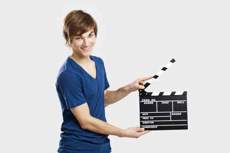 Casual young man holding a clapboard, over a gray background photo