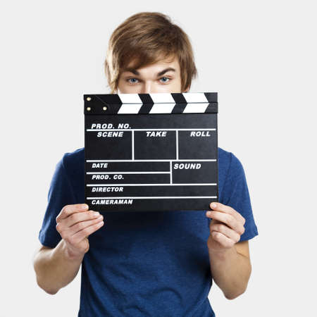 Portrait of a young man peeking behind a clapboard, over a gray background Stock Photo - 13359329