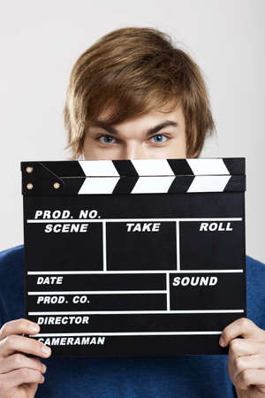 Portrait of a young man peeking behind a clapboard, over a gray background photo