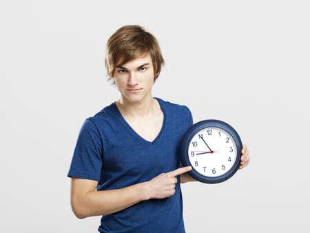 Portrait of a young man holding a clock over a gray background Stock Photo - 13359376