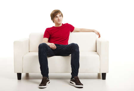 Handsome young man at home sitting on the couch Stock Photo
