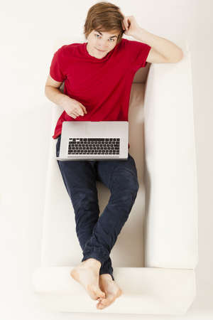 Relaxed young man at home lying on the couch with a laptop photo