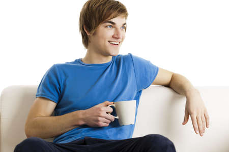Young man sitting on the couch drinking a cup of coofee photo