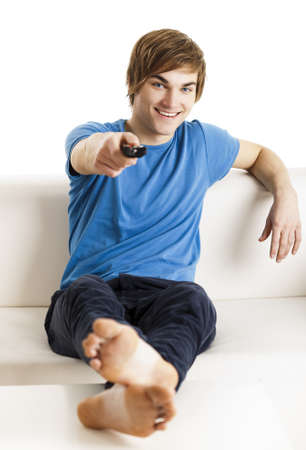 Young man sitting on the couch using a remote control Stock Photo
