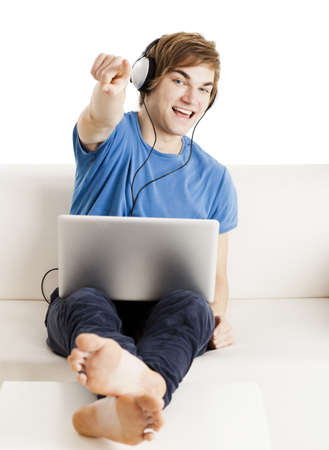Happy young man sitting on the couch with arms up and a laptop over the legs photo