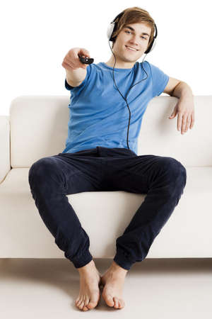 Young man sitting on the couch using a remote control Stock Photo - 13359285