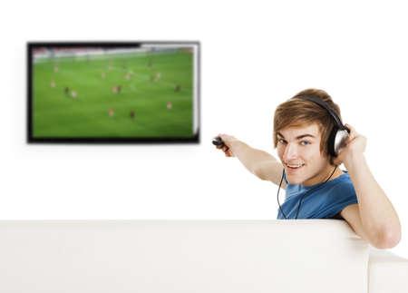 personas viendo television: Joven sentado en el sof� con un mando a distancia y ver un partido de f�tbol en la tele