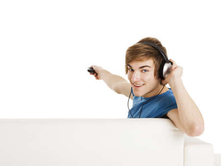 Young man sitting on the couch using a remote control, with copyspace for the designer photo